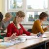 Billede af kvinde i klasseværelse som læser med sin PlexTalk Linio Pocket