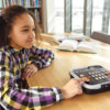 Billede af pige der sidder på biblioteket med sin Victor Reader Stratus 12M