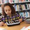 Billede af pige på biblioteket der læser med sin Victor Reader Stratus 12M