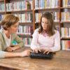 Billede af pige på biblioteket sammen med en underviser og BrailleNote Touch Plus