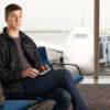 Mand sidder med Brailliant i loungen i lufthavnen