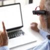 Mand læser på pc med OrCam MyEye i fokus