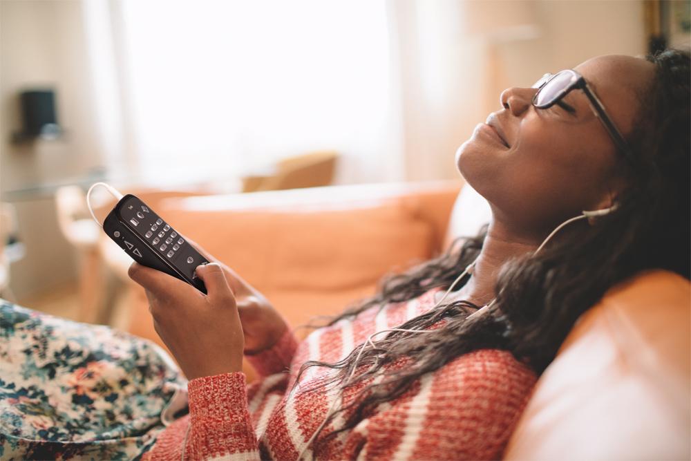 Kvinde lytter til music eller podcasts med Victor Reader Trek