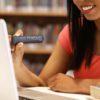 Ung kvinde læser på computer med OrCam Read