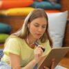 Ung kvinde læser på iPad med OrCam Read