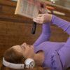 Ung kvinde ligger ned og læser med OrCam Read